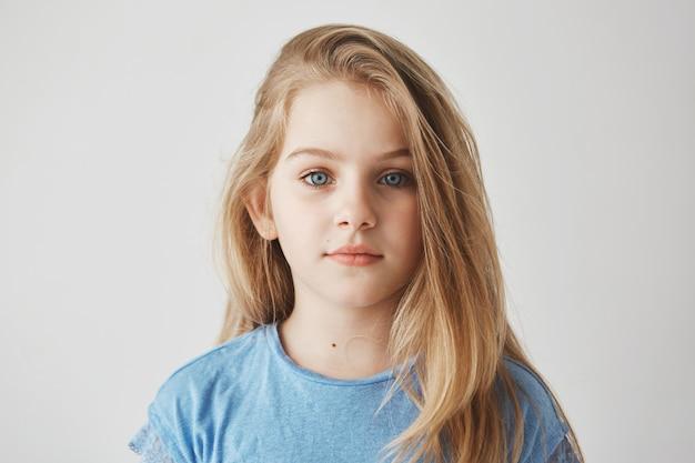 가벼운 긴 머리를 가진 아름 다운 작은 소녀와 편안한 표정으로 큰 파란 눈의 초상화를 닫습니다.