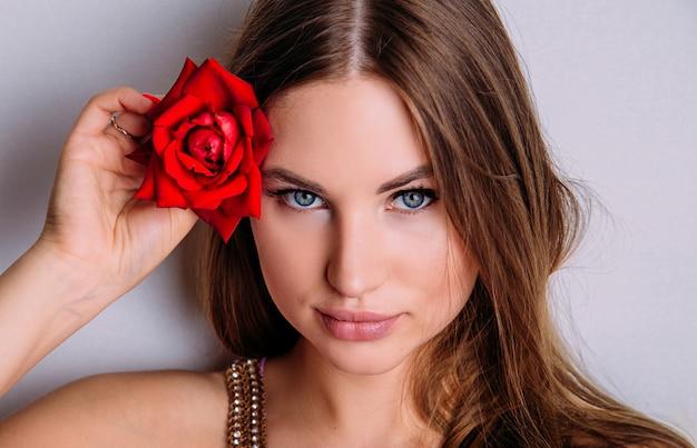 彼女の手に赤いバラと美しいモデルの女性のクローズアップの肖像画。