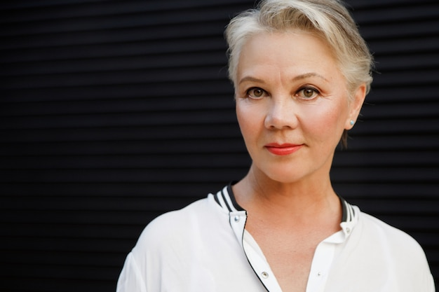 黒髪の白い髪の美しい年配の女性のクローズアップの肖像画