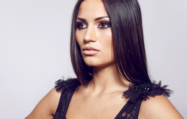 Крупным планом портрет красивой чувственной женщины с длинными прямыми волосами и ярким макияжем, над белой