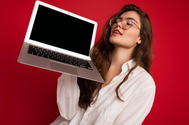 分離されたカジュアルなスマートな服を着て楽しんでネットブックを見てコンピュータラップトップを保持している美しい笑顔の幸せな若い女性のクローズアップの肖像画