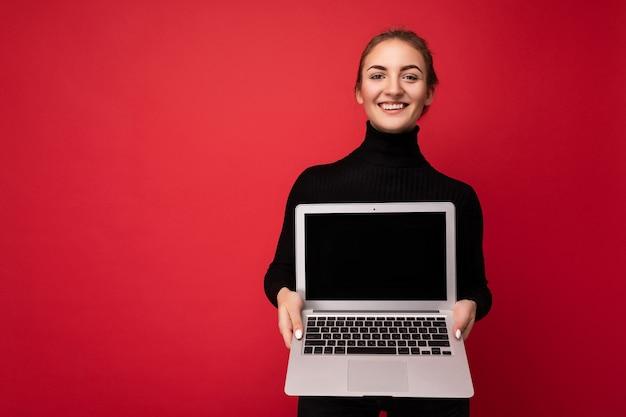 Крупным планом портрет красивой улыбающейся счастливой молодой женщины с собранными темными волосами, держащей компьютерный ноутбук с пустым экраном монитора с макетом в черном лонгсливе, смотрящем на камеру.