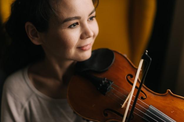 Крупным планом портрет красивой улыбающейся молодой женщины-музыканта, играющего на скрипке