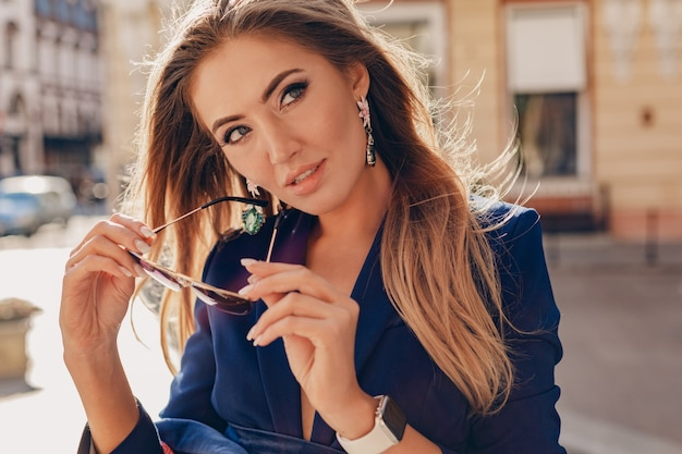 エレガントなサングラスとイヤリングを身に着けている秋の日当たりの良い通りを歩くスタイリッシュな青いジャケットに身を包んだ美しい女性のクローズアップの肖像画