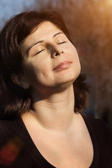 Крупным планом портрет красивой женщины улыбается с закрытыми глазами над солнечным светом, медитация на открытом воздухе