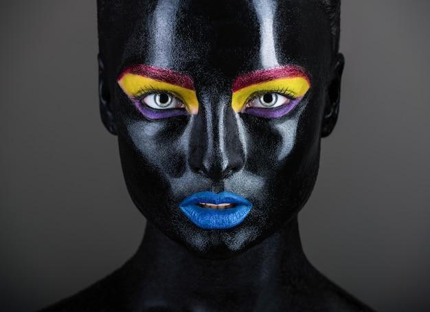 Крупным планом портрет красивой женщины с боди-артом на лице в черном и цветном на темном фоне