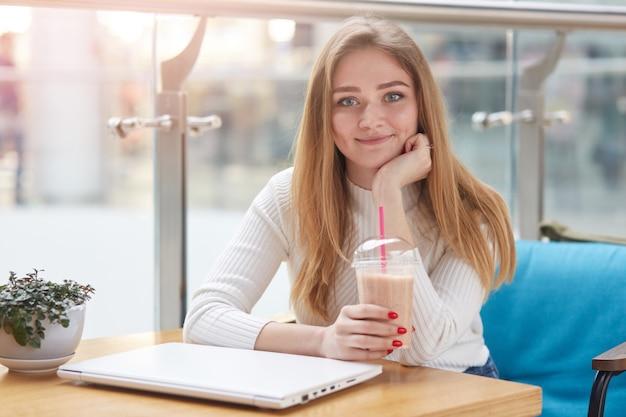 긴 금발 머리 카페에 앉아 우유 칵테일을 마시는, 노트북에 온라인 작업 후 나머지는 데 카메라에 직접보고 아름 다운 젊은 백인 여자의 초상화를 닫습니다.