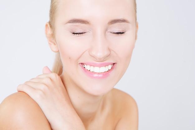 分離した、白い歯を持つ美しい若い幸せな笑顔の女性の肖像画を間近します。