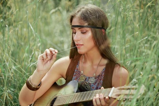 Закройте вверх. портрет красивой молодой женщины хиппи с гитарой, сидящей на лесной поляне