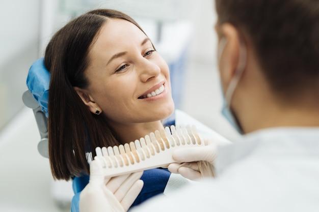 Крупным планом портрет красивой молодой леди, сидящей в стоматологическом кресле, в то время как стоматолог руки в стерильных перчатках с образцами зубов