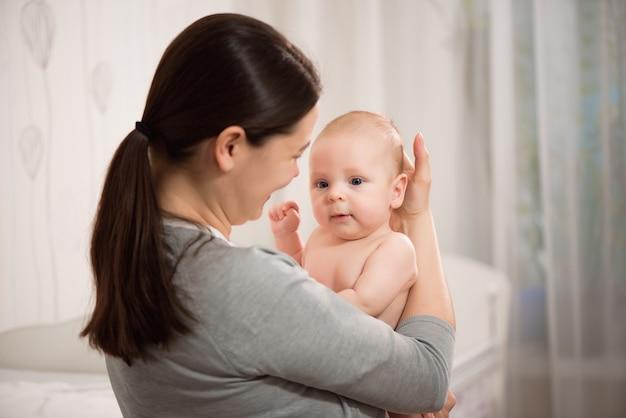 그녀의 신생아를 키스하는 아름 다운 젊은 어머니 여자의 초상화를 닫습니다.