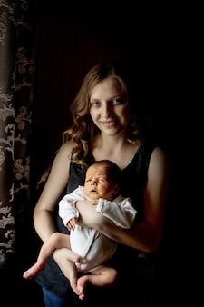 검은 배경, 복사 공간에 신생아와 함께 아름 다운 젊은 어머니의 초상화를 닫습니다. 건강 관리 및 의료 사랑의 라이프 스타일 어머니.