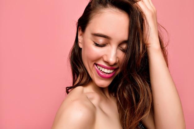 ピンクの壁に目を閉じて白い歯とピンクの唇を持つ美しい若い笑顔の女性の肖像画をクローズアップ