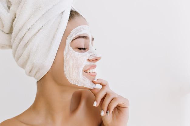 걸릴 목욕 후 수건으로 웃는 아름 다운 젊은 여자의 클로즈업 초상화는 그녀의 얼굴에 화장품 마스크를 확인합니다.