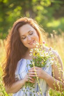 晴れた夏に美しい野花の花束を嗅ぐ美しい若い女性のクローズアップの肖像画