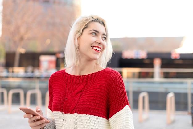 Крупным планом портрет красивой молодой женщины, использующей мобильный телефон на открытом воздухе в городе