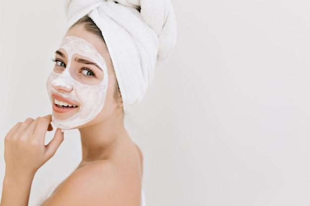 걸릴 목욕 후 수건으로 아름 다운 젊은 여자의 클로즈업 초상화는 그녀의 얼굴에 화장품 마스크를 확인합니다.