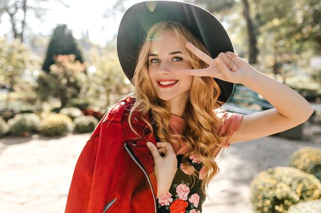公園でピースサインを示す黒いつばの広い帽子と赤いジャケットの盲目の女性のクローズアップの肖像画。
