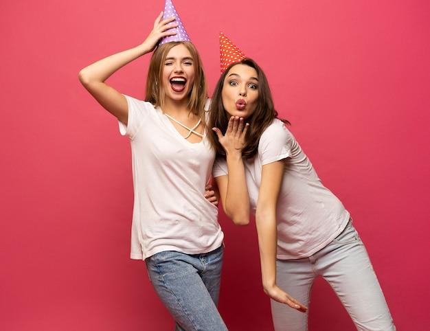 Закройте вверх по портрету молодых женщин блондинки и брюнетки с шляпами дня рождения весело изолированными на розовом фоне.