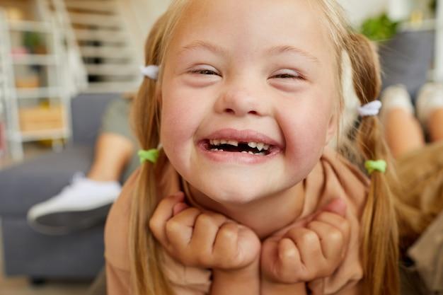집에서 소파에 누워있는 동안 행복하게 웃는 다운 증후군 금발 소녀의 초상화를 닫습니다