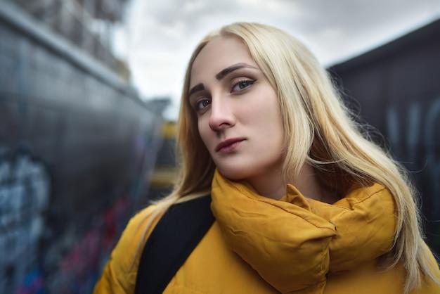 금발 힙 스터 십대 소녀 만들기 셀카의 초상화를 닫습니다, 그녀는 노란색 재킷과 배낭을 입고있다