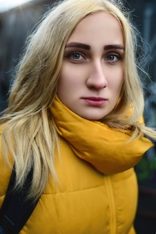 Крупным планом портрет блондинки-хипстера-подростка, делающей селфи, она носит желтую куртку и рюкзак