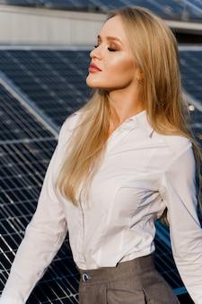 Портрет крупным планом блондинки возле солнечных батарей
