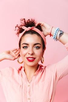 ピンクのシャツに身を包んだ赤い口紅と孤立した空間に巨大なイヤリングを持つ青い目の女性のクローズアップの肖像画。