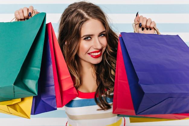 カラフルなパッケージを保持している黒い爪を持つ青い目の女性のクローズアップの肖像画。笑顔の至福の黒髪の女の子の屋内写真