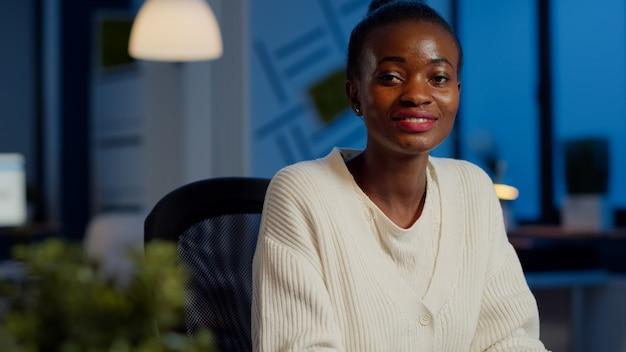 カメラで笑っているビジネスアフリカの女性の肖像画をクローズアップ