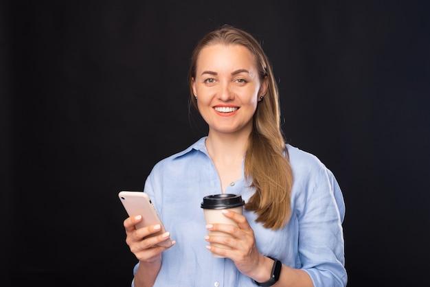 스마트폰과 종이 커피 컵을 들고 웃고 있는 비즈니스 여성의 초상화를 클로즈업