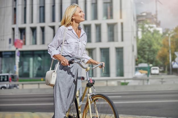 도시의 현대적인 건물 근처에서 복고풍 자전거를 타고 가는 백인 여성 사업가의 초상화를 클로즈업