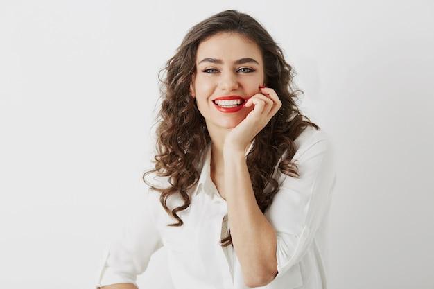 孤立した白い歯、長い巻き毛、白いブラウス、エレガントなビジネススタイル、幸せな肯定的な感情、赤い口紅メイクと率直な笑顔の魅力的な女性のポートレートを閉じます