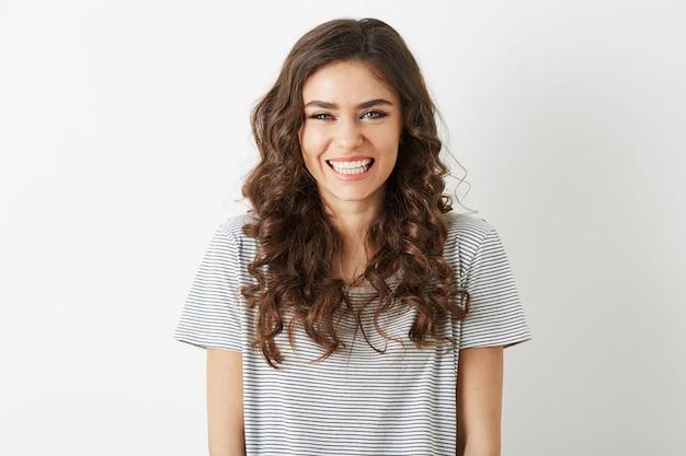 흰색 배경, 긴 곱슬 머리, 간단한 티셔츠, 캐주얼 힙 스터 스타일, 행복 긍정적 인 감정에 고립 된 하얀 치아와 솔직한 웃는 매력적인 여자의 초상화를 닫습니다