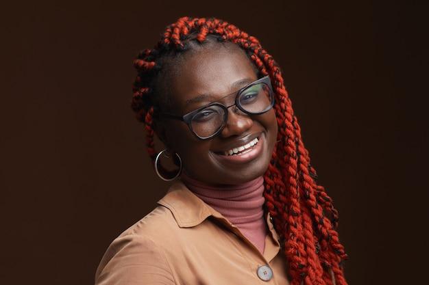 スタジオで暗い茶色の背景にポーズをとっている間、カメラに微笑んでいる編みこみの髪を持つのんきなアフリカ系アメリカ人女性の肖像画をクローズアップ、コピースペース