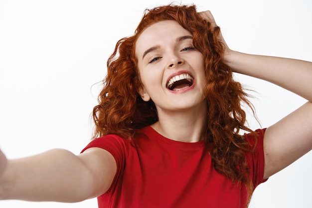 Крупным планом портрет беззаботной и счастливой рыжей девушки, касающейся ее вьющихся натуральных волос и смеющейся во время селфи на белой стене