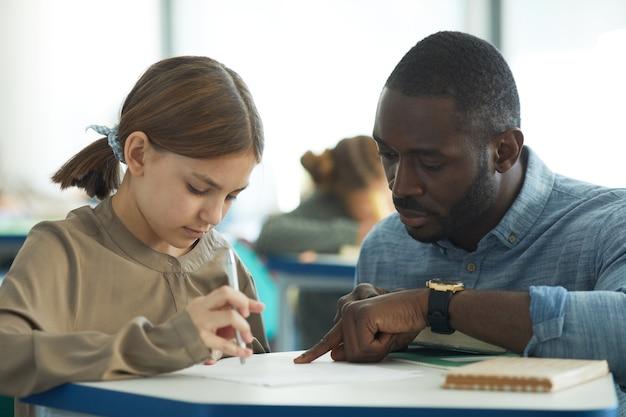 Крупным планом портрет заботливого учителя-мужчины, помогающего молодой девушке в школьном классе