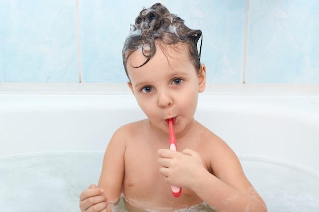 Крупным планом портрет carming маленькая девочка, чистит зубы с красной зубной щеткой