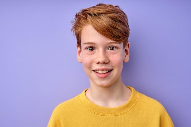 紫色のスタジオの背景に分離された、目を大きく開いて変な顔を作るカジュアルな服装の白人少年のクローズアップの肖像画。ショックを表現する少年興奮、魅惑、真の本物の感情