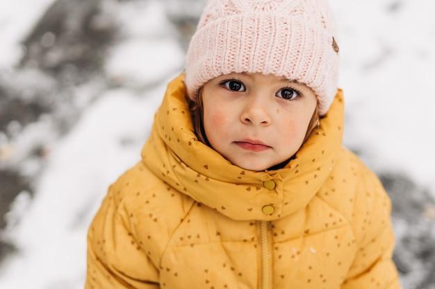 Закройте вверх по портрету кавказской девушки малыша с красными щеками в зимний день. . фото высокого качества