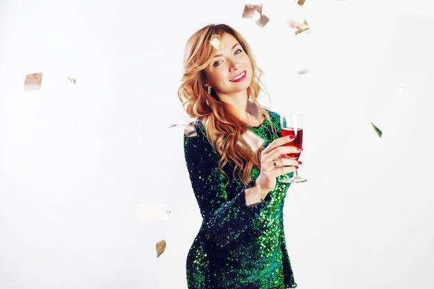 パーティーを楽しんで、ワインを飲む緑のスパンコールドレスでお祝いの女性の肖像画を閉じます。黄金の紙吹雪。