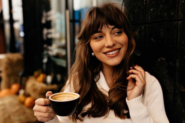 一杯のコーヒーと魅力的なブルネットの女性のクローズアップの肖像画。