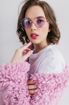 Портрет крупным планом очаровательной кавказской женской модели в фиолетовых очках. вдохновленная брюнетка с волнистыми волосами.