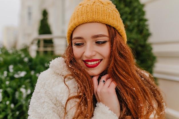 モミの近くに立っている魅力的な生姜の女性のクローズアップの肖像画。冬の帽子でうれしそうな笑顔の女の子の屋外写真。