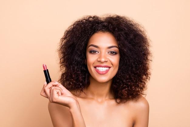 魅力的な女の子のクローズアップの肖像画は、ベージュのパステルカラーの壁に分離されたピンクの口紅を保持します