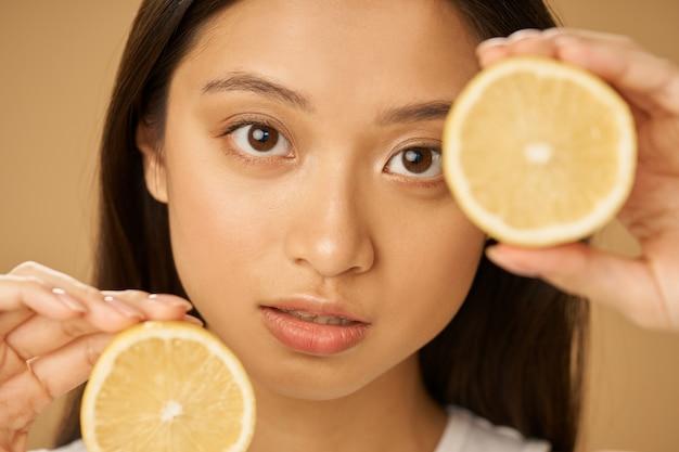 Крупным планом портрет очаровательной молодой женщины смешанной расы, смотрящей в камеру, держа разрезанный пополам лимон