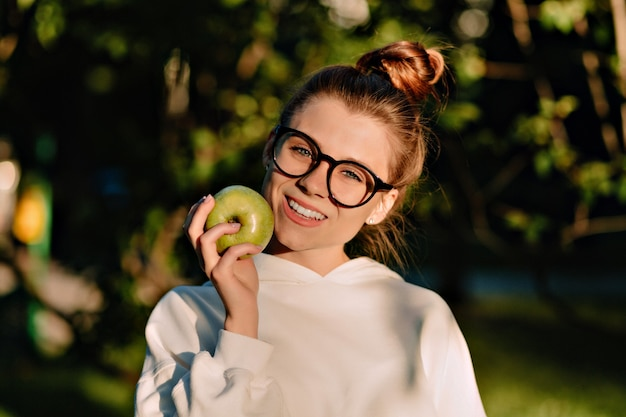 公園で日光の下でリンゴを食べる壮観なものを身に着けている魅力的なきれいな女性の肖像画をクローズアップ