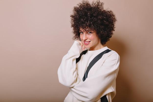 흰색 스웨터를 입고 매력적인 예쁜 여자의 클로즈 업 초상화는 분홍색에 재미와 미소를 가지고