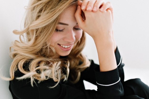 Крупным планом портрет очаровательной красивой женщины со светлыми вьющимися волосами, улыбаясь с закрытыми глазами