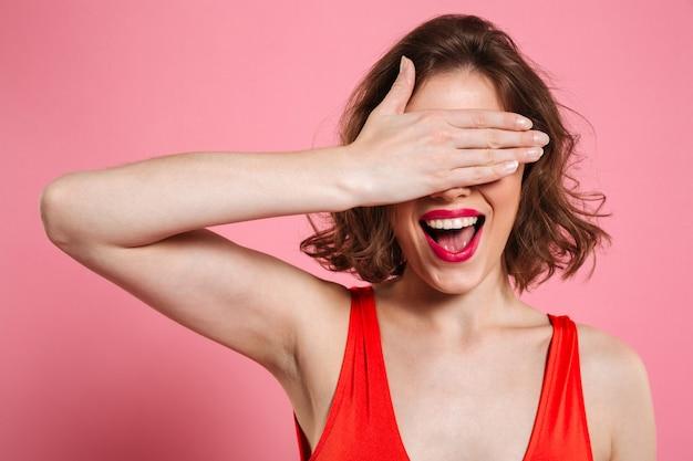 손 아래 눈을 숨기고 매력적인 웃는 갈색 머리 여자의 클로즈 업 초상화
